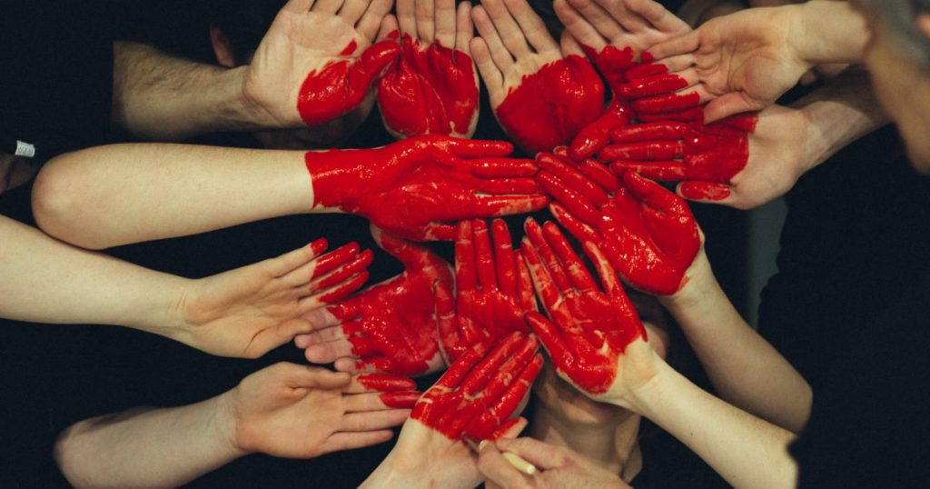 Hands formed together with red painted heart